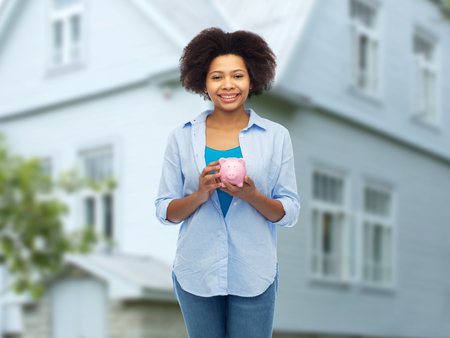 people, investment, saving and finances concept - happy afro american young woman with piggy bank over house background