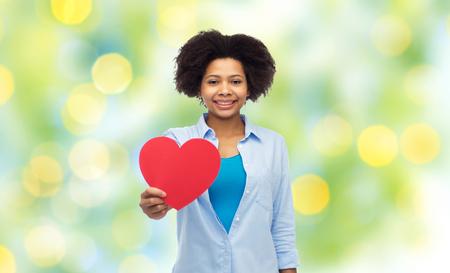 forme et sante: les gens, amour, Saint Valentin et le concept de santé - heureux jeune femme afro-américaine avec forme de coeur rouge sur vert été lumières fond