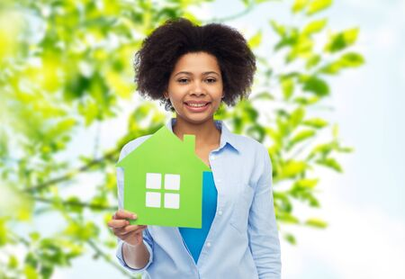 nice accommodations: people, home and real estate concept - happy african american young woman with green house icon over green natural background Stock Photo