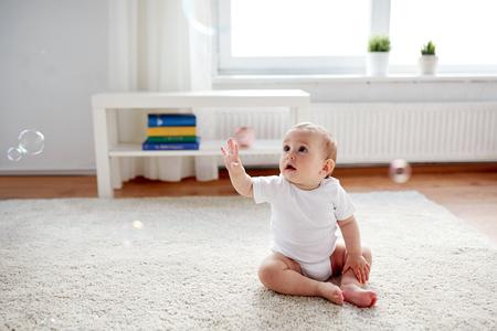 bebe sentado: la infancia, la infancia y las personas concepto - Feliz niño o niña sentada en el suelo con las burbujas de jabón por su casa