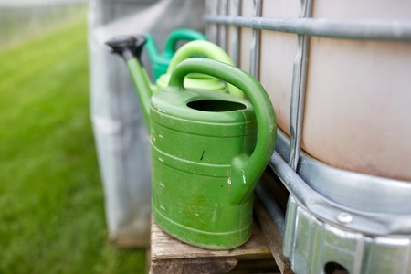 bailer: farming, gardening and agriculture concept - watering cans at farm water tank