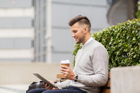 creative communication: business, education, technology, communication and people concept - creative man with tablet pc computer drinking coffee from paper cup and sitting on city street bench