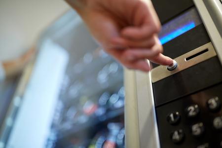 prodej, technologie a koncept spotřeby - ruční stisknutí tlačítka na ovládacím panelu prodejního automatu Reklamní fotografie