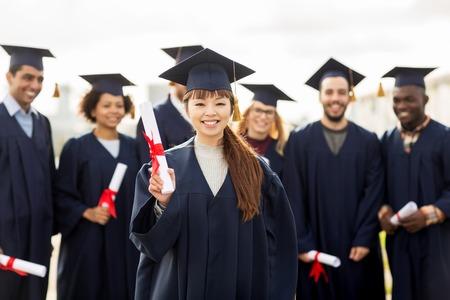教育、卒業および人々 のコンセプト - モルタル ボードや卒業証書と学士のガウンで幸せな国際学生のグループ