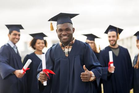 親指を現して卒業証書と幸せな学生