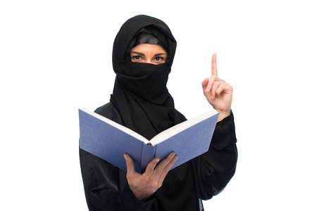 coran: muslim woman in hijab with book over white