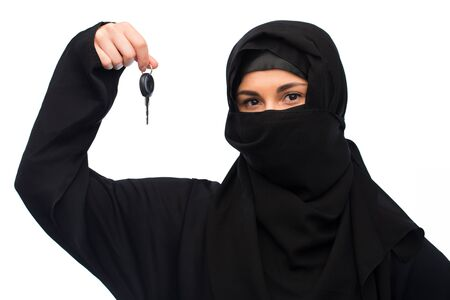 paranja: muslim woman in hijab with car key over white