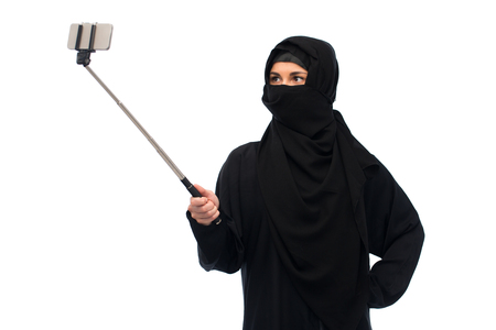 muslim woman in hijab taking selfie by smartphone