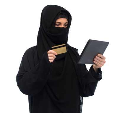 paranja: woman in hijab with tablet pc and credit card Stock Photo