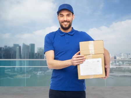 deliverer: happy delivery man with boxes over singapore city