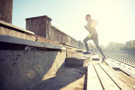 upstairs: happy young man running upstairs on stadium