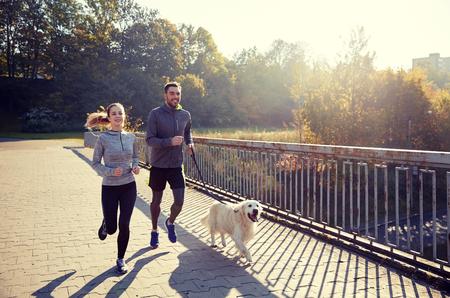 gelukkig echtpaar met hond in openlucht loopt Stockfoto