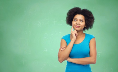 femmes souriantes: pensive afro american  woman over green chalkboard Banque d'images