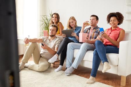 amigos con aparatos y cerveza viendo la televisión en casa Foto de archivo