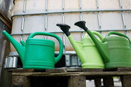 bailer: watering cans at farm water tank Stock Photo