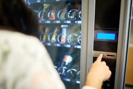 woman pushing button on vending machine