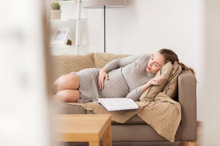 happy pregnant woman sleeping on sofa at home Stock Photo
