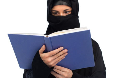 yashmak: muslim woman in hijab reading book over white