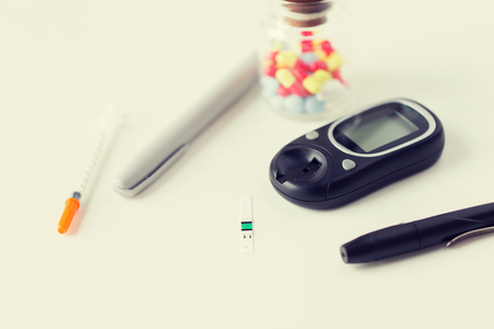medicine, diabetes and health care concept - close up of blood sugar test stripe, glucometer, insulin pen and other diabetic tools on table