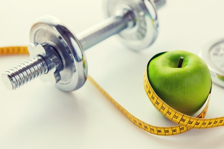 sport, fitness, diet and objects concept - close up of dumbbell and green apple with measuring tape Stock Photo