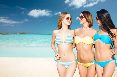 travel background: summer holidays, travel, people and vacation concept - happy young women in bikinis and shades over exotic tropical beach background