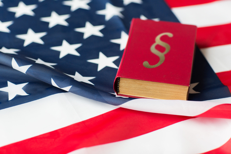 justice, law, civil rights and nationalism concept - close up of american flag and lawbook Stock Photo