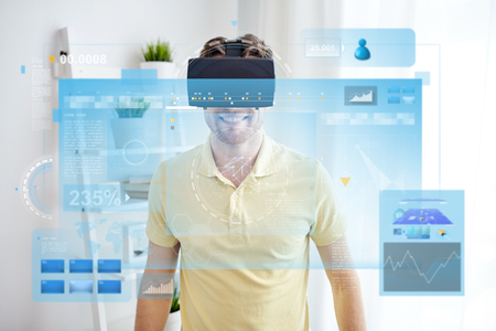 technology, augmented reality, big data and people concept - happy young man with virtual headset or 3d glasses looking at screens projection Foto de archivo