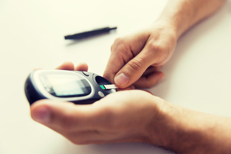 medicine, diabetes, glycemia, health care and people concept - close up of man checking blood sugar level with glucometer and test stripe at home