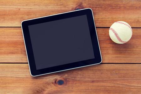 baseball stuff: close up of baseball ball and tablet pc on wood Stock Photo
