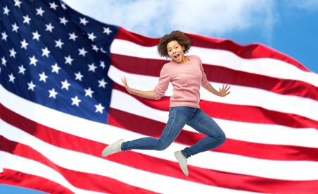 people, motion and action concept - happy african young woman jumping over american flag background Stock Photo