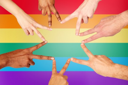 diversity, gay pride, tolerance, international and people concept - group of hands showing peace hand sign over rainbow background Reklamní fotografie