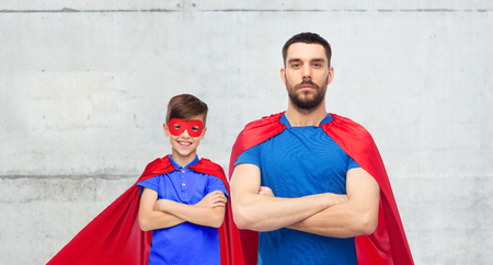 family, power and people concept - man and boy wearing mask and red superhero cape over gray concrete wall background