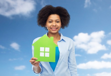 people, home and real estate concept - happy african american young woman with green house icon over blue sky and clouds background