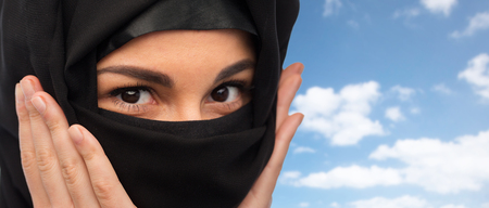 paranja: religious and people concept - close up of muslim woman in hijab over blue sky and clouds background