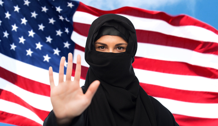 yashmak: gesture, immigration, religious prohibition and people concept - muslim woman in hijab showing stop sign over american flag background