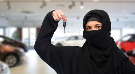 paranja: property and people concept - muslim woman in hijab with car key over car show background
