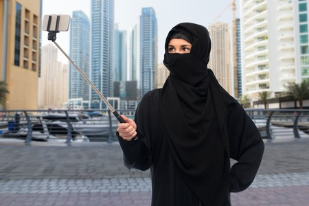 paranja: technology and people concept - muslim woman in hijab taking picture with smartphone selfie stick over dubai city street background