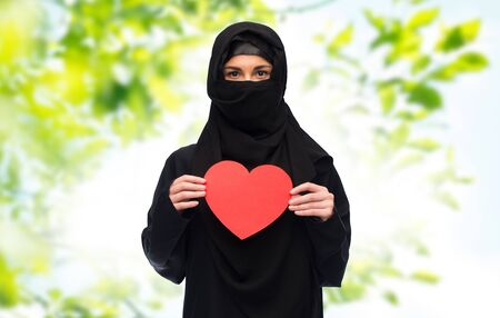 paranja: love, charity, valentines day and people concept - muslim woman in hijab holding red heart over green natural background