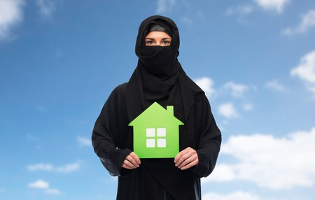 yashmak: ecology and people concept - muslim woman in hijab with green house over blue sky and clouds background