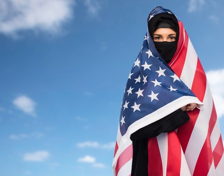 paranja: immigration and people concept - muslim woman in hijab with american flag over blue sky and clouds background