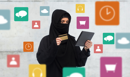 paranja: finances, technology, online shopping and people concept - muslim woman in hijab with tablet pc computer credit card over gray concrete wall background