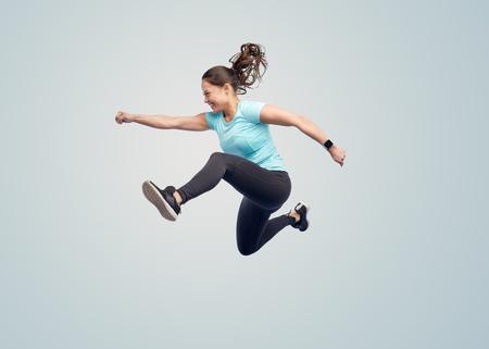 사람: 스포츠, 피트니스, 운동과 사람들 개념 - 행복 파란색 배경 위에 공중에서 점프 웃는 젊은 여자