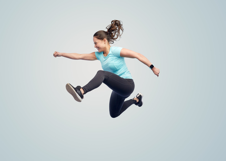 fitness girl: sport, fitness, motion and people concept - happy smiling young woman jumping in air over blue background