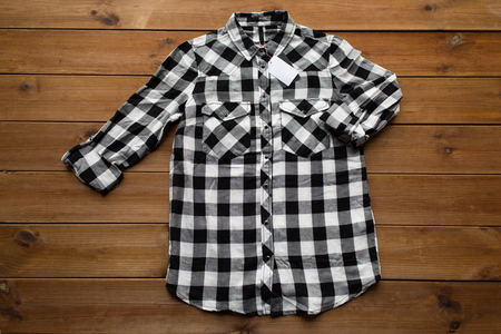fashion dress: clothes, fashion and objects concept - checkered shirt with price tag on wooden background Stock Photo