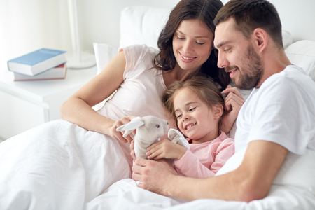 people, family and morning concept - happy child with toy rabbit and parents in bed at home Stock Photo
