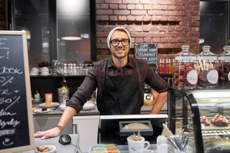 happy seller man or barman at cafe counter