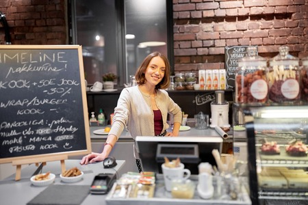 saleslady: happy woman or barmaid at cafe counter