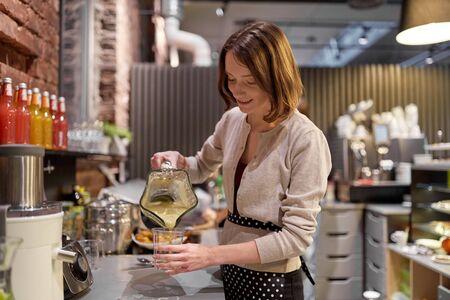salesgirl: woman or barmaid cooking smoothie at vegan cafe Stock Photo