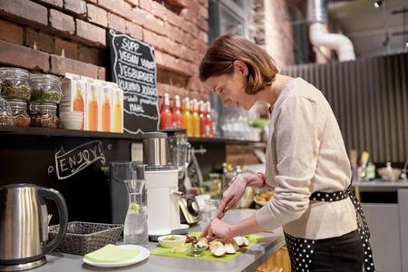 salesgirl: happy woman or barmaid cooking at vegan cafe