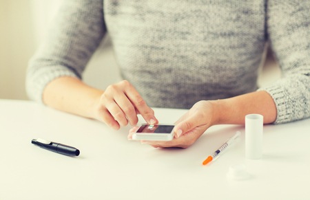 hyperglycemia: close up of woman with smartphone doing blood test Stock Photo